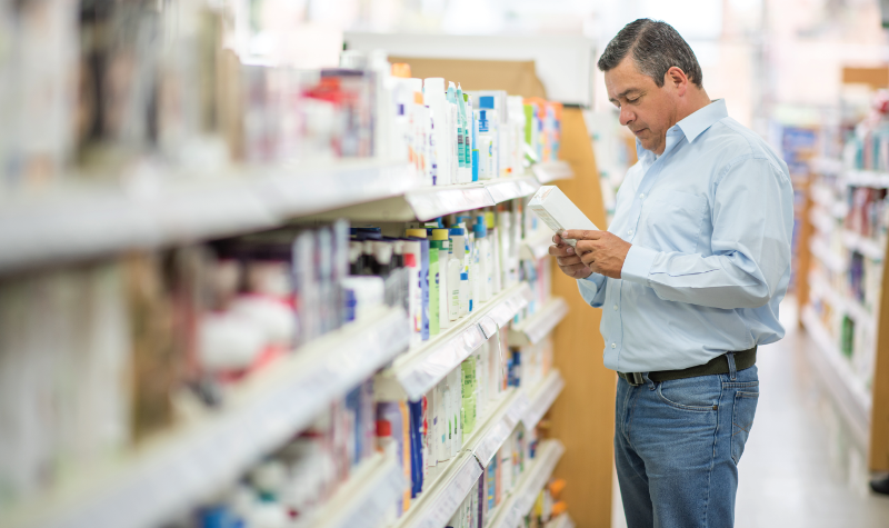 Man in pharmacy looking at boxes